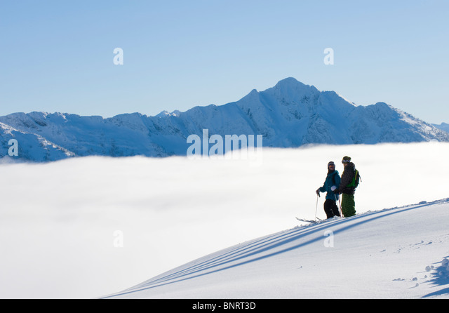 Two men traversing on skis, BC, Canada. - Stock Image