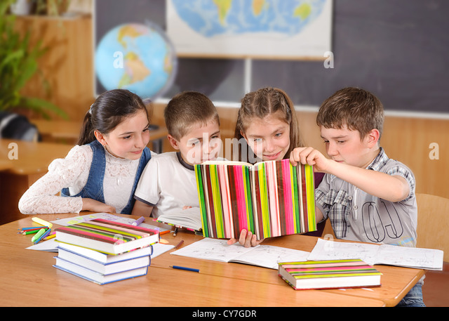Four elementary aged pupils reading book in classroom - Stock Image