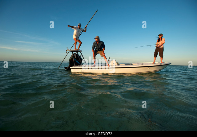 A woman fishes while one man watches and one man pilots the boat in Florida. - Stock Image
