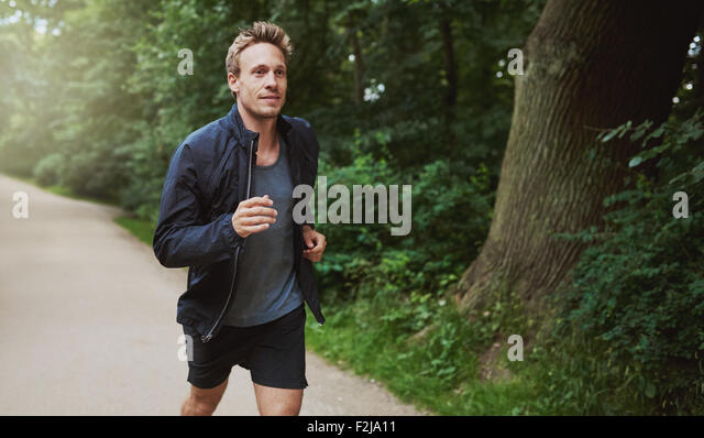 Three Quarter Shot of a Healthy Young Man in Jacket Shirt, Jogging at the Park Early in the Morning. - Stock Image