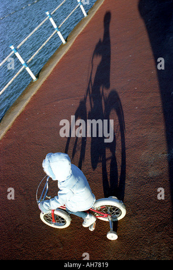 A child on a bicycle fitted with stabilisers casting a shadow - Stock Image