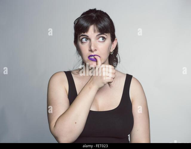 Studio Shot Of Young Woman Biting Her Nail - Stock Image