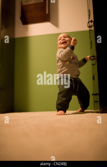 Toddler boy taking first steps - Stock Image