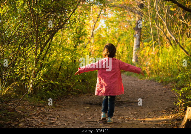 Happy female toddler strolling through autumn woodland - Stock Image