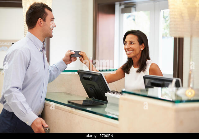 Man Checking In At Hotel Reception - Stock Image