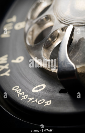 a detail of an old-fashioned rotary phone dial with shallow depth of field and focus on 0 for an operator - Stock Image