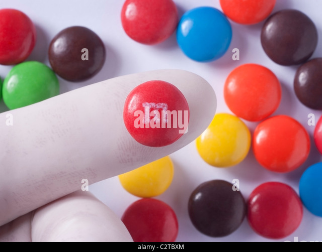 Gloved finger holding candy sold in the United States that contains Artificial Food Coloring that may cause ADHD - Stock Image