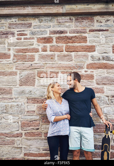 Three Quarter Shot of a Happy Sweet Couple with Skateboard, Smiling at Each Other Against Concrete Wall Background. - Stock-Bilder