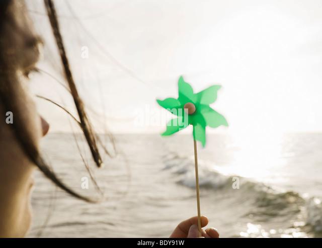 Woman holding windmill towards sea - Stock Image