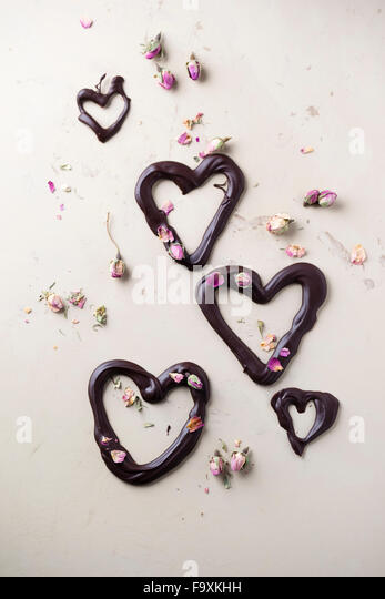 Chocolate hearts and dried rose blossom on light ground - Stock Image