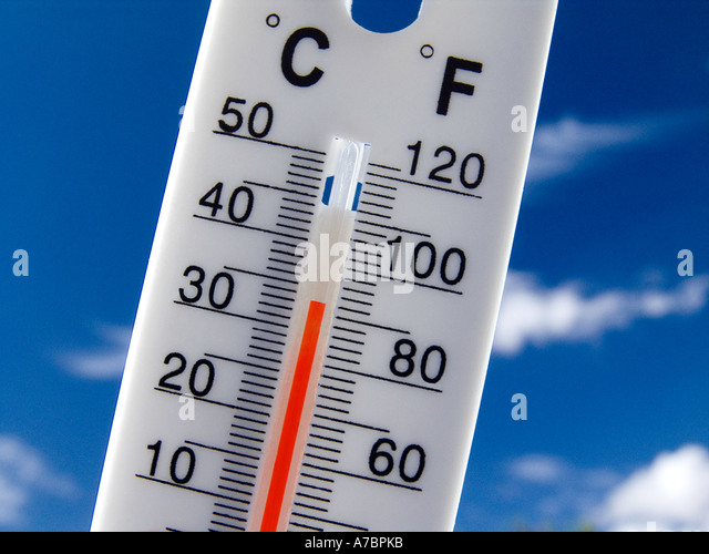 Thermometer displays a hot and sunny 34 degrees centigrade  81 degrees farenheit against a bright blue sky - Stock Image