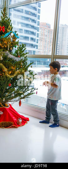 Young boy at home, decorating Christmas tree, deciding where to place decoration - Stock Image