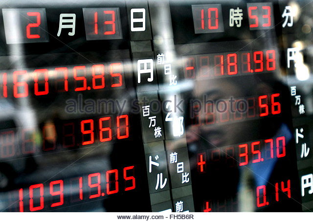 Businessman is reflected in a nikkei stock market screen in downtown
