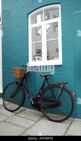 An Old Bike Leaning Against A Blue Painted Brick Wall - Stock Image