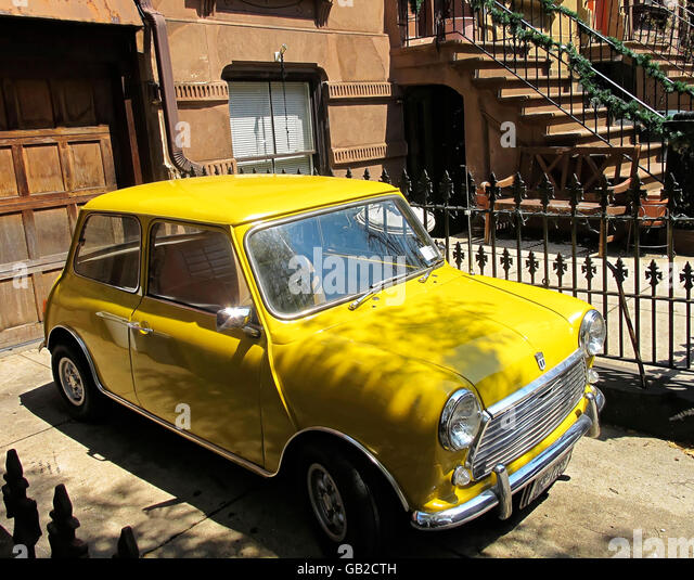 Bright yellow mini car parked by a brownstone home. - Stock Image