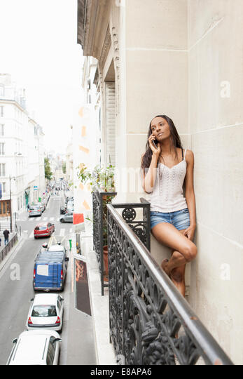 Woman using phone on balcony, Paris, France - Stock Image