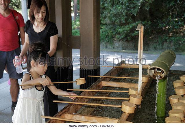 Tokyo Japan Shibuya-ku Meiji Jingu Shinto Shrine temizuya font washing water hands feet mouth dipper Asian girl - Stock Image