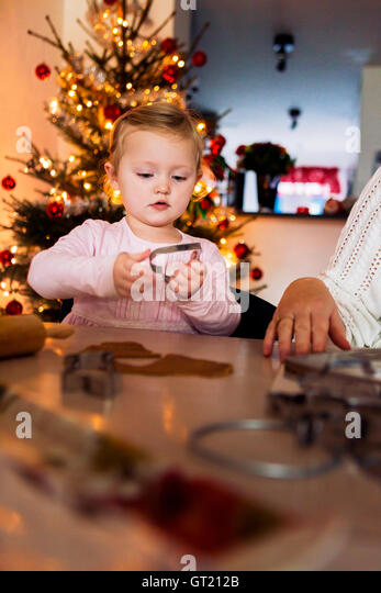 Girl holding pastry cutter while sitting besides mother at table - Stock-Bilder