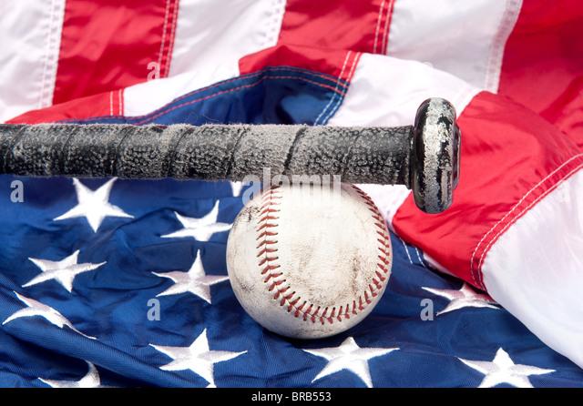 Baseball equipment including a bat and a baseball on an American flag. - Stock Image