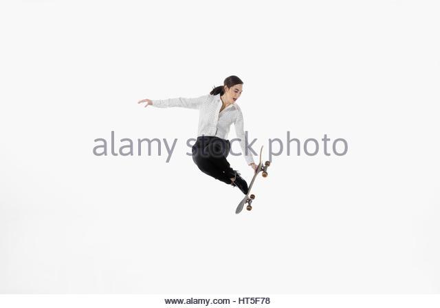 Businesswoman with skateboard jumping against white background - Stock-Bilder