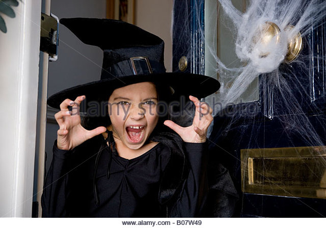 Young girl at the front door, dressed up as a witch for Halloween - Stock Image