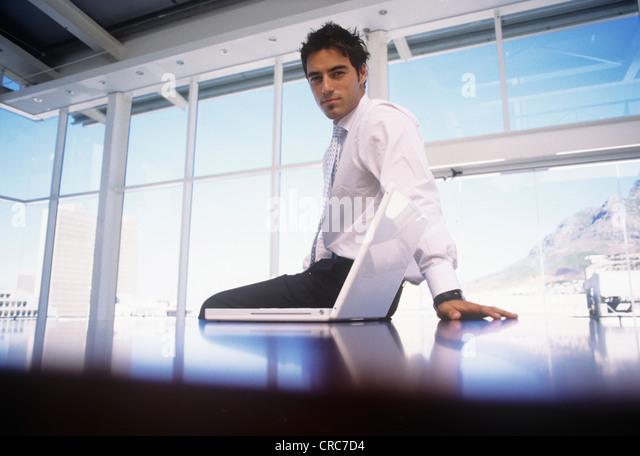 Businessman sitting on desk in office - Stock-Bilder