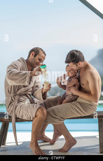 Gay couple making a bottle for the baby at the poolside - Stock Image