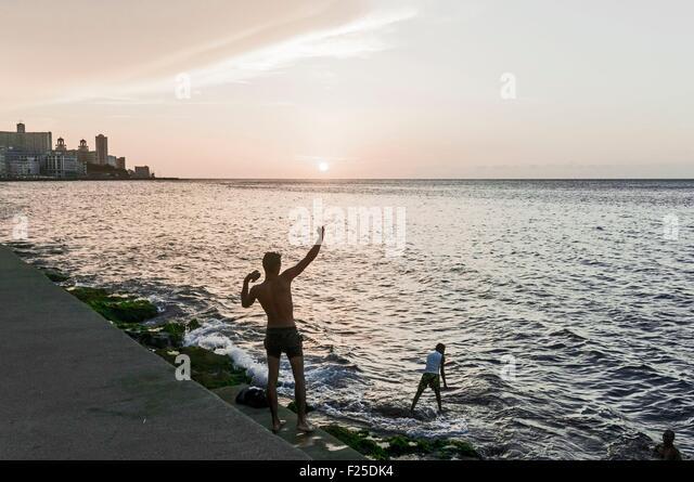 Cuba, Havana, fishermen and Vedado quarter buildings on Malecon - Stock Image