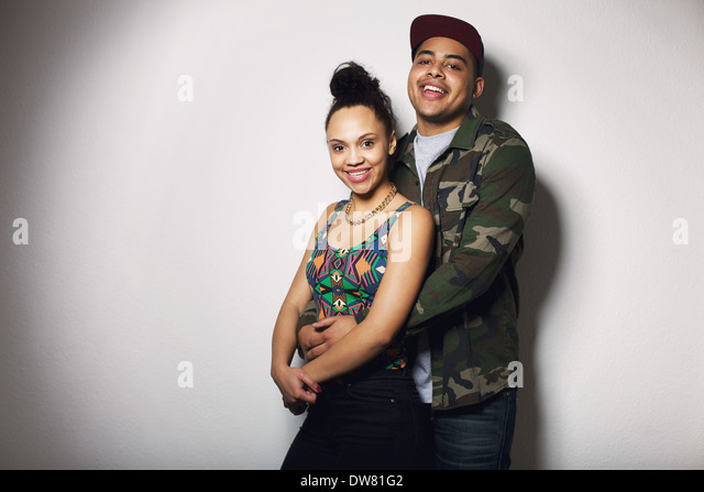 Portrait of young man and woman standing against grey background with lots of copy space. Beautiful young couple - Stock Image