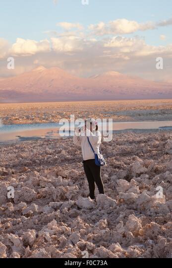 Young girl taking photograph of arid landscape of Salar de Atacama, San Pedro, Atacama, Chile - Stock Image