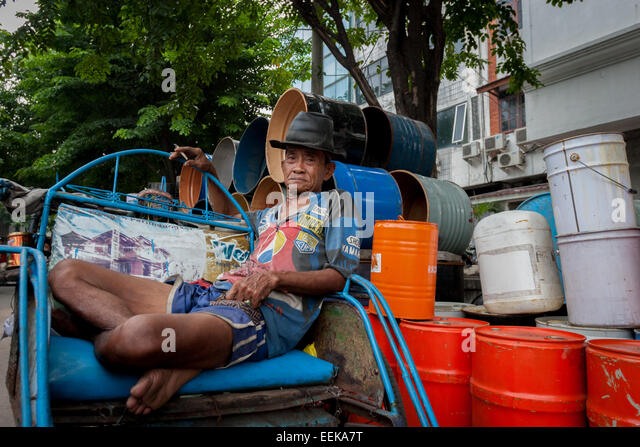 Becak (cycle rickshaw) driver relaxing, waiting for passenger. - Stock Image