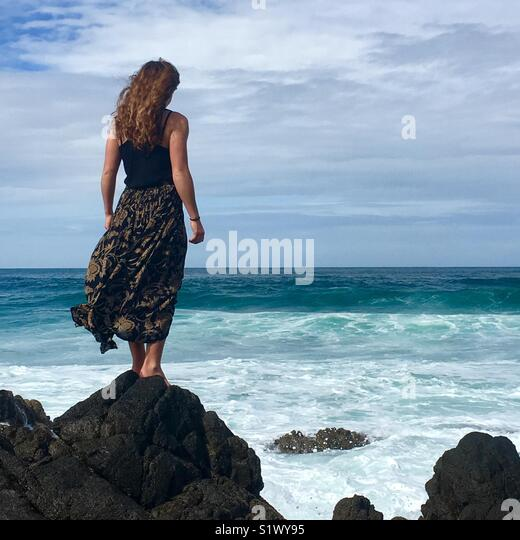 Girl stands on rocks looking out to sea - Stock Image