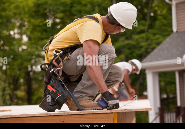 Carpenters laying a snap line on a particle board using chalk line - Stock Image