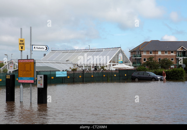 Lady retrieves car from water in Weymouth after heavy rains flooded the car park - Stock Image