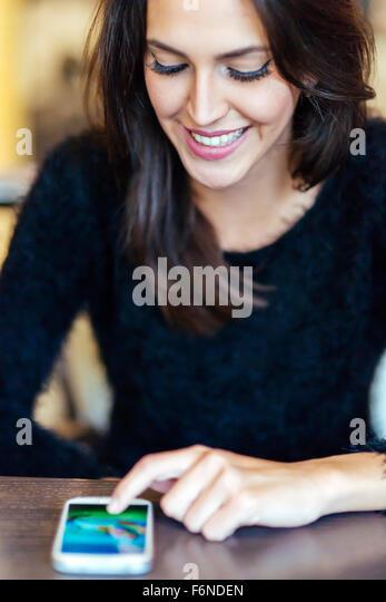 Beautiful brunette tapping phone - Stock-Bilder