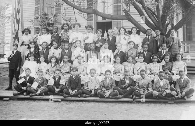 Full length landscape portrait of African American schoolchildren, all wearing uniforms, first three rows seated, - Stock Image