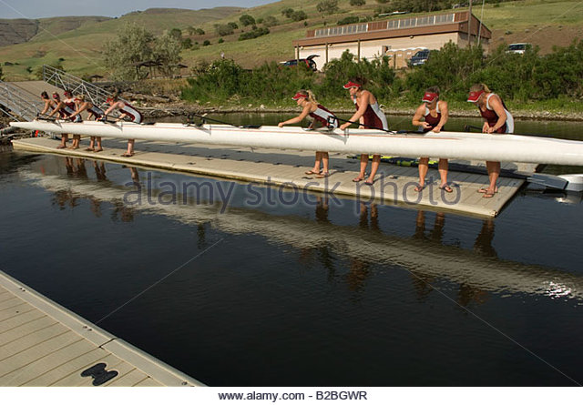 Rowing team lowering scull into water - Stock Image