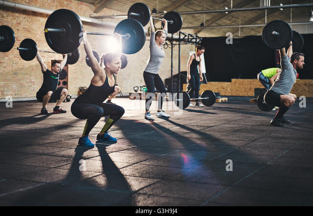 Fit young people lifting barbells over their heads looking focused, working out in a gym with other people - Stock Image
