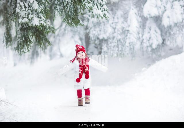 Funny laughing toddler girl running in a beautiful snowy park - Stock Image