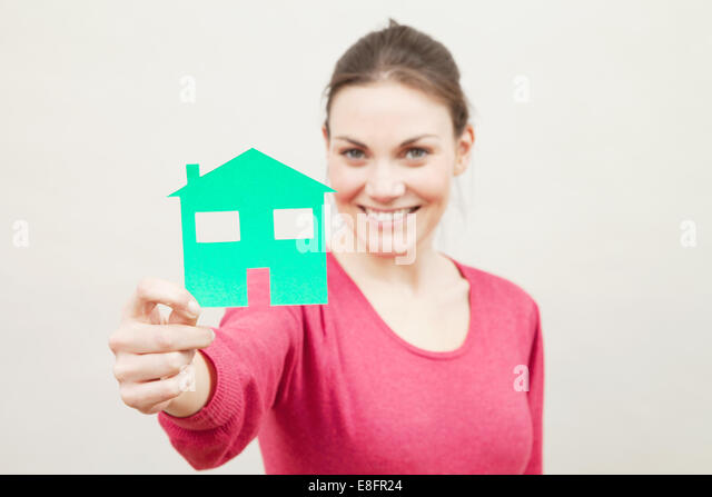Young woman holding paper cut out of recycling symbol - Stock Image