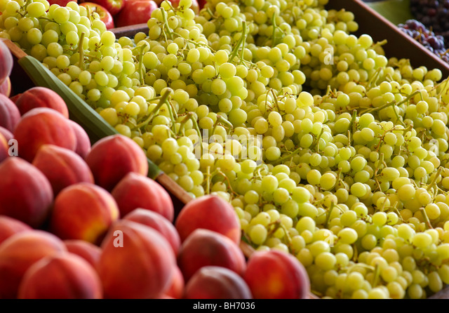 Fresh grapes and peaches at greengrocer's - Stock Image