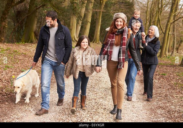 Couple Taking Dog For Walk On City Street - Stock Image