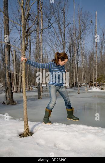 Woman Testing Ice on Pond - Stock Image