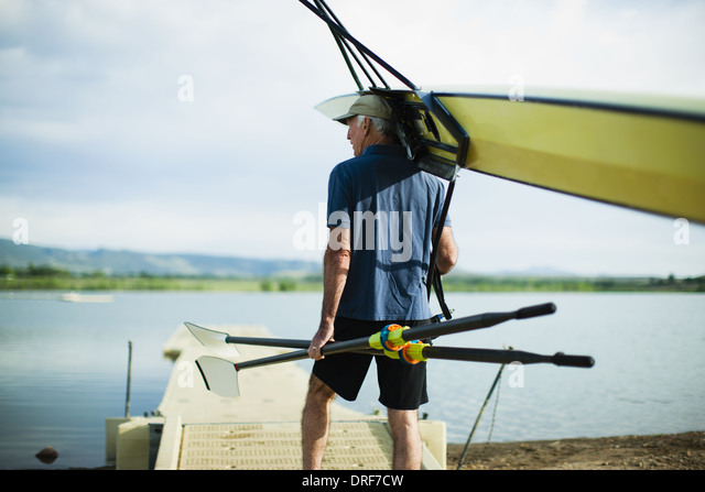 Colorado USA middle-aged man carrying oars and rowing shell - Stock Image