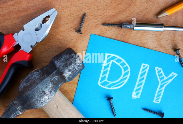 Blue paper with diy Do It Yourself, tools kit on a wood background - Stock Image