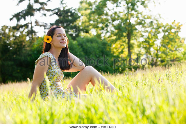 Carefree brunette woman with flower in hair in sunny summer rural grass - Stock-Bilder