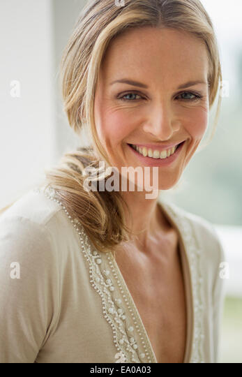 Mature blonde woman looking at camera smiling, portrait - Stock Image