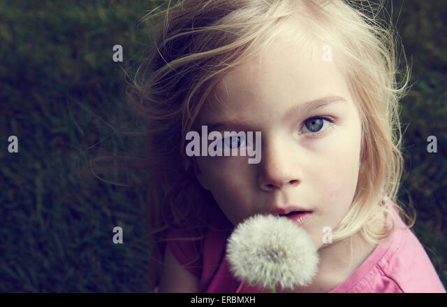 Portrait of caucasian blond girl blowing flower dandelion seeds - Stock Image