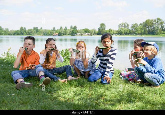 Children enjoying slices of watermelon at picnic, Munich, Bavaria, Germany - Stock Image