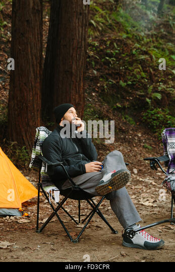 A young man sits around the camp site in Big Sur, California. - Stock Image
